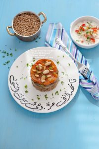 Eggplant Maqloobeh & Tahini Salad on Arabic Calligraphy Plate and blue background